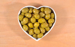 Green olives in plate in form of heart Stock Photo