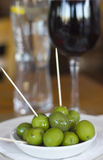 Green Olives and Red Wine. Shiny Green Olives in a White Bowl with Red Wine and Water Stock Photos
