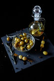 Green olives with rosemary and olive oil in a bottle. Green olives on picks with rosemary and olive oil in a bottle with herbs Royalty Free Stock Photo