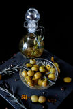 Green olives with rosemary and olive oil in a bottle. Green olives on picks with rosemary and olive oil in a bottle with herbs Royalty Free Stock Photography