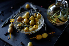 Green olives with rosemary and olive oil in a bottle. Green olives on picks with rosemary and olive oil in a bottle with herbs Stock Photo