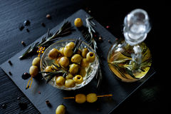 Green olives with rosemary and olive oil in a bottle. Green olives on picks with rosemary and olive oil in a bottle with herbs Royalty Free Stock Photos