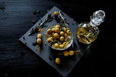 Green olives with rosemary and olive oil in a bottle. Green olives on picks with rosemary and olive oil in a bottle with herbs Stock Photography