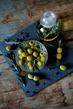 Green olives with rosemary and olive oil in a bottle. Green olives on picks with rosemary and olive oil in a bottle with herbs Stock Image