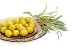 Green olives on saucer and olive branch closeup. Fragment of a dark glass saucer with canned green olives and olive branch beside on a white background Royalty Free Stock Photos
