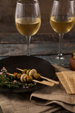 Green olives served in plate by crackers with white wine Royalty Free Stock Photography