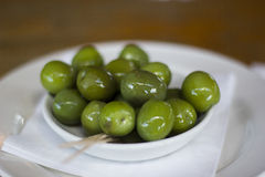 Green Olives. Shiny Green Olives in a White Bowl Stock Photo