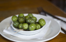 Green Olives. Shiny Green Olives in a White Bowl Stock Photos