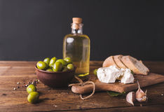 Green olives, sliced ciabatta, feta cheese on a wooden board. Olive oil in a glass bottle. Cheese Feta. Ciabatta. Olives on a black  background Royalty Free Stock Photography