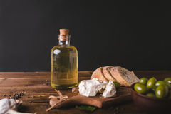 Green olives, sliced ciabatta, feta cheese on a wooden board. Olive oil in a glass bottle. Cheese Feta. Ciabatta. Olives on a black background Stock Image