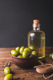 Green olives, sliced ciabatta, feta cheese on a wooden board. Olive oil in a glass bottle. Cheese Feta. Ciabatta. Olives on a black background Royalty Free Stock Images