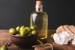 Green olives, sliced ciabatta, feta cheese on a wooden board. Olive oil in a glass bottle. Cheese Feta. Ciabatta. Olives on a black background Royalty Free Stock Photos