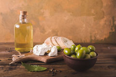 Green olives, sliced ciabatta, feta cheese on a wooden board. Olive oil in a glass bottle. Cheese Feta. Ciabatta. Olives on a orange abstract background Stock Image