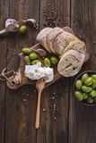 Green olives, sliced ciabatta, feta cheese on a wooden board. Spice. Garlic. Chees Feta. Ciabatta. Olives on a wooden background. Royalty Free Stock Images