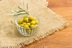 Green olives in small glass bowl and olive branch closeup. Canned green olives in small glass bowl and olive branch on a sackcloth on a surface of an old wooden Royalty Free Stock Photos