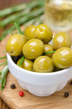 Green olives and spices on a wooden board, close-up vertical Stock Photography