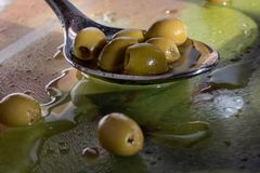 Green olives in a spoon stock photo