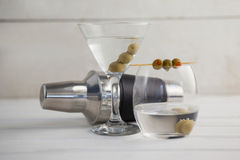 Green olives in vodka martini with cocktail shaker. On wooden table Royalty Free Stock Photo