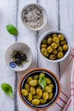 Assortment of olives with herb and sea salt on white wooden back Royalty Free Stock Photo