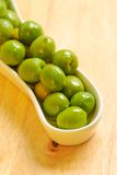 Green olives in white plate Stock Photos