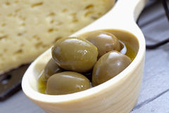 Green olives in wooden bowl cheese in background, close up Stock Photo