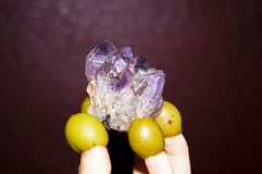 Amethyst crystal in the hands of green olive fingers stock photos