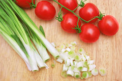 Green onion and red tomatoes. Royalty Free Stock Image