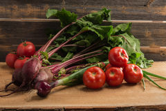 Green onions, beet and tomatoes against the background of old grey boards. Fresh green onions, beet and tomatoes against the background of old grey boards in stock image
