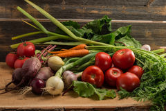 Green onions, garlic, carrots, beet and tomatoes against the background of old grey boards. Fresh green onions, garlic, carrots, beet and tomatoes against the Stock Photography
