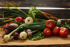 Green onions, garlic, carrots, beet and tomatoes against the background of old grey boards. Fresh green onions, garlic, carrots, beet and tomatoes against the royalty free stock photo