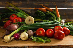 Green onions, garlic, carrots, beet and tomatoes against the background of old grey boards. Fresh green onions, garlic, carrots, beet and tomatoes against the Royalty Free Stock Photography