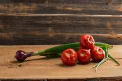 Green onions and tomatoes against the background of old boards. Fresh green onions and tomatoes against the background of old boards in rustik style stock photo