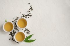 Green oolong tea. Green tea in ceramic cups, dry green oolong tea and tea leaves on white stone table, top view, copy space stock images