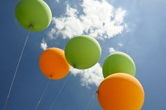 Green and orange balloons flying towards the sun. Green and orange air balloons flying towards the sun with clouds and blue sky background Stock Photos