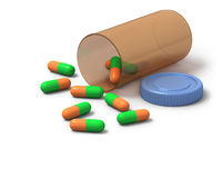 Green and orange capsules on white background Stock Image