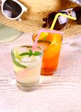 Green, orange cocktails with straw and holiday background Royalty Free Stock Photography
