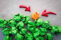 Green and orange crumpled paper balls  with red arrow Stock Photos
