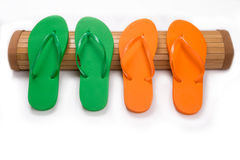 Green and Orange Flip Flops on Bamboo Mat With Copy Space Stock Image