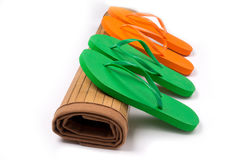 Green and Orange Flip Flops on Rolled Bamboo Mat Stock Image