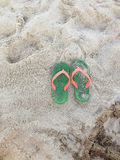 Green Orange Flipflops on a sandy. Summer vacation concept. Green Orange Flipflops on a sandy ocean beach royalty free stock photography