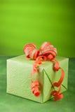 Green & orange gift box. Green present with orange ribbon and green background Stock Photo