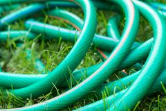 A green and orange hose for watering the garden. Close up royalty free stock image