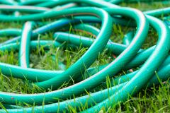 A green and orange hose for watering the garden. Close up stock image