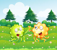 A green and an orange monster near the pine trees Royalty Free Stock Photos