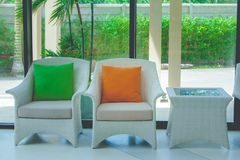 Green and orange pillows on white weave chair setting on concrete floor in the lobby of hotel. Green and orange pillows on white weave chair setting on concrete royalty free stock photo