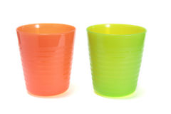 plastic cups. Green and orange plastic cups on white Royalty Free Stock Images