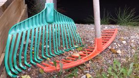 Green and orange rake. Green and orange plastic rakes for yardwork stock photography