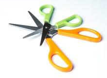 Green and orange scissors on white background Stock Photo