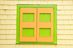 Green and Orange Shutters on Yellow Siding House Royalty Free Stock Photography