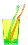 Green and orange toothbrushes in glass Stock Photo